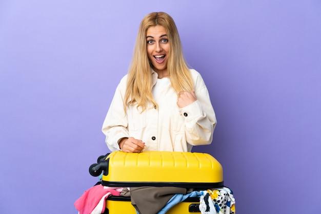 Jeune femme blonde uruguayenne avec une valise pleine de vêtements sur un mur violet isolé avec une expression faciale surprise
