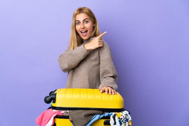 Jeune femme blonde uruguayenne avec une valise pleine de vêtements sur le mur violet isolé surpris et pointant le côté