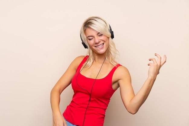 Jeune femme blonde en utilisant le mobile avec des écouteurs et danser