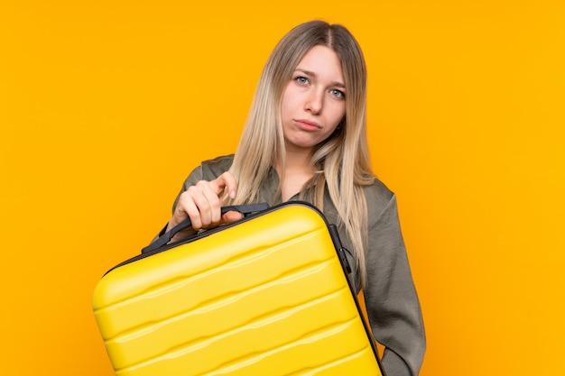 Jeune femme blonde en vacances avec valise de voyage et malheureux