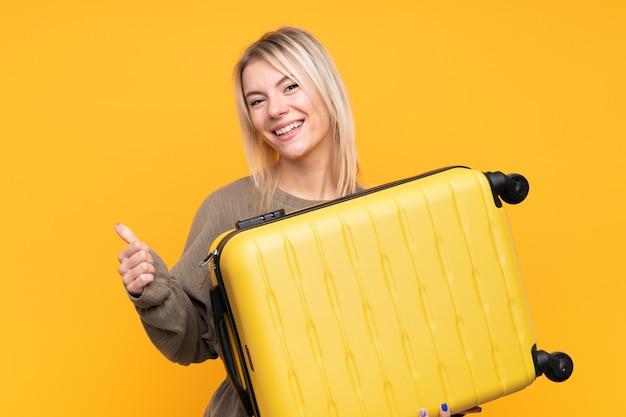 Jeune femme blonde en vacances avec valise de voyage et avec le pouce vers le haut