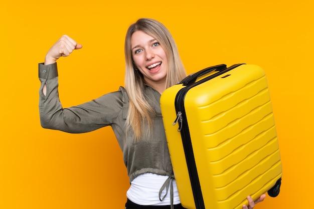 Jeune femme blonde en vacances avec valise de voyage