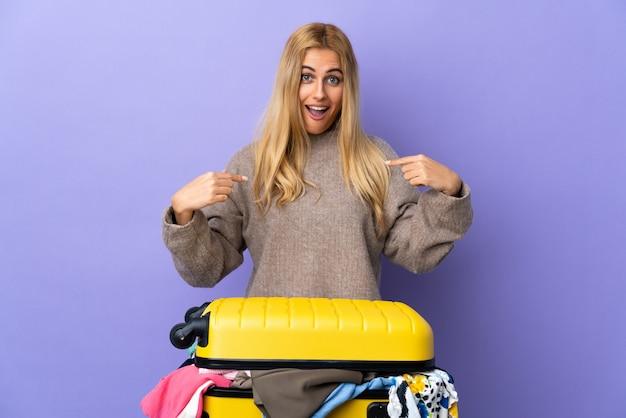Jeune femme blonde avec une valise pleine de vêtements sur un mur violet isolé avec une expression faciale surprise