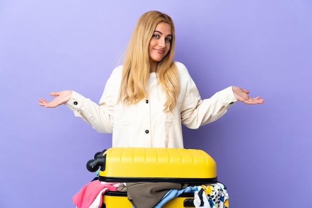 Jeune femme blonde avec une valise pleine de vêtements sur mur violet isolé heureux et souriant