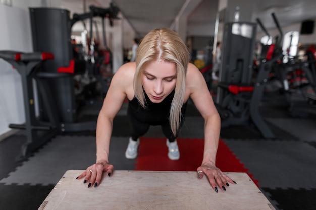 Jeune femme blonde en vêtements noirs sportifs s'entraîne dans la salle de gym