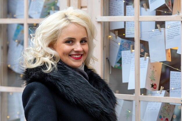 Jeune femme blonde à la vitrine avec des voeux de noël. le concept de noël.