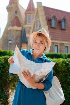 Jeune femme blonde voyageuse dans un chapeau et des lunettes de soleil avec une carte des sites touristiques d'un autre pays. vacances d'été et liberté de loisirs actifs et concept de mode de vie actif