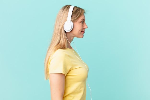 Jeune femme blonde en vue de profil pensant, imaginant ou rêvant et écoutant de la musique.