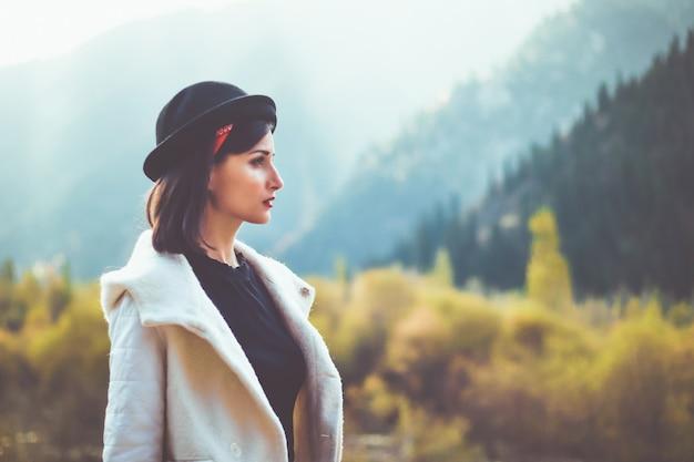 Une jeune femme en blouse blanche marchant dans la nature détourne le regard se mettre à l'abri du froid d'automne