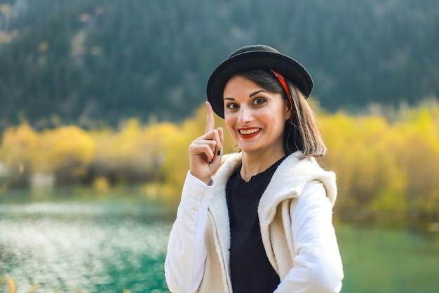 Une jeune femme en blouse blanche marchant dans la nature, regarde la caméra, l'index vers le haut