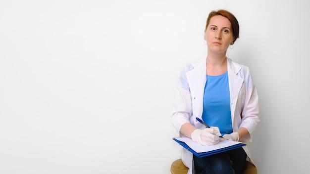 Jeune femme en blouse médicale blanche assise sur une chaise avec dossier, stylo et feuille de papier pour les notes