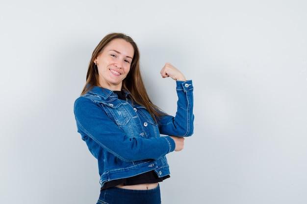 Jeune femme en blouse montrant le poing fermé et l'air confiant, vue de face.