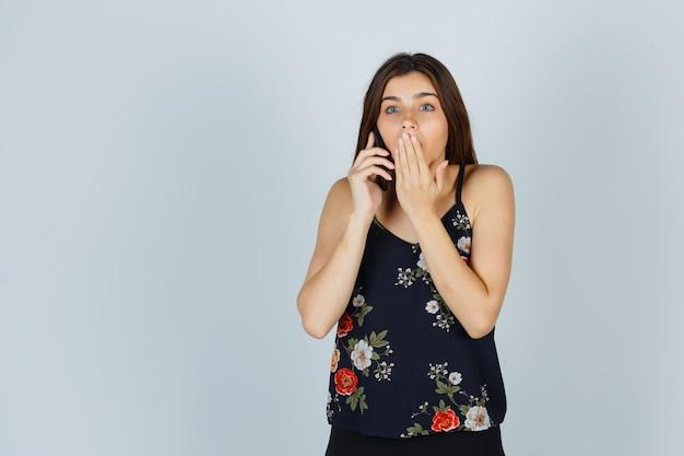 Jeune femme en blouse parlant sur smartphone, tenant la main sur la bouche et l'air surpris, vue de face.