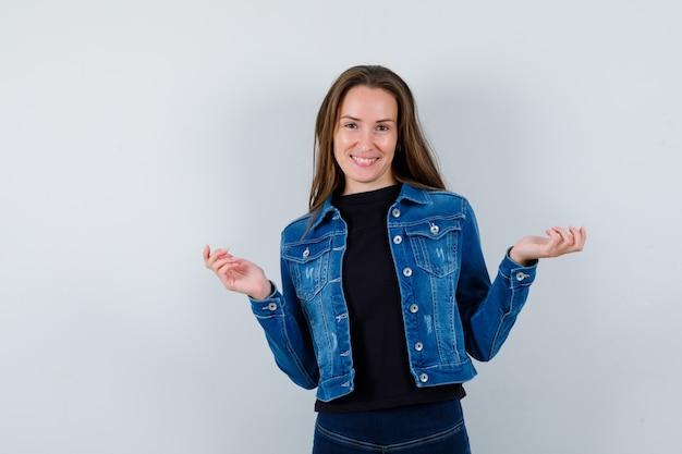 Jeune femme en blouse posant tout en écartant les paumes et l'air optimiste, vue de face.