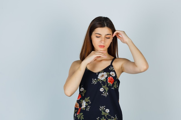 Jeune femme en blouse posant tout en touchant la peau de son visage et l'air délicieuse, vue de face.