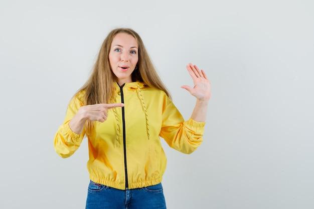 Jeune femme en blouson aviateur jaune et jean bleu montrant un panneau d'arrêt avec une main et pointant vers elle et à l'optimiste, vue de face.