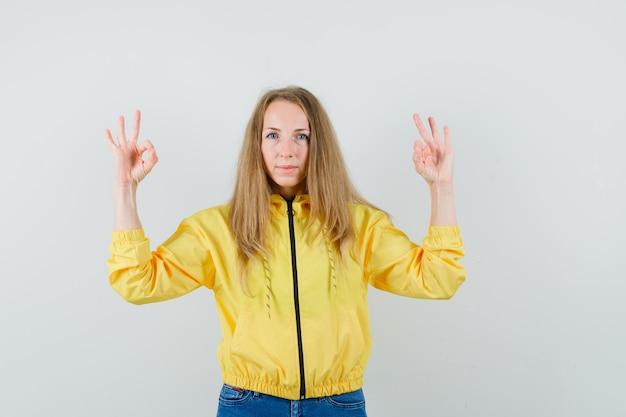 Jeune femme en blouson aviateur jaune et jean bleu montrant le signe ok avec les deux mains et à la grave, vue de face.