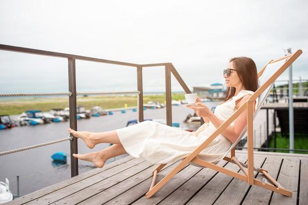 Jeune femme, boire, café chaud, apprécier, vue plage.
