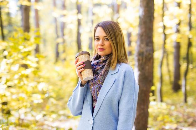 Jeune femme, boire, café, dans, automne, parc