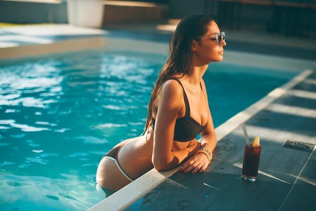 Jeune femme, boire, coctail, par, piscine, à, chaud, jour été