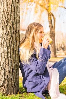 Jeune femme, boire, sous, arbre, dans, automne, parc