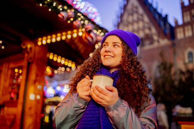 Jeune femme avec boisson sur le marché de noël à wroclaw, pologne