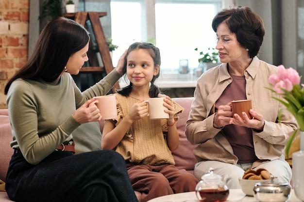 Jeune femme avec une boisson touchant la tête de sa petite fille mignonne tout en prenant le thé