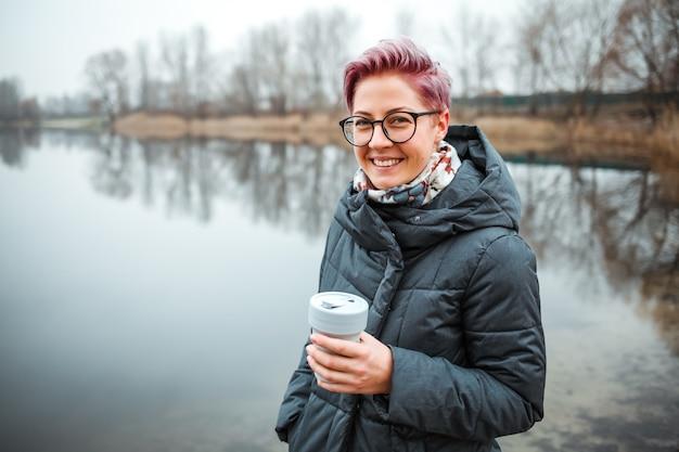 Jeune femme boit une tasse de café au bord du lac