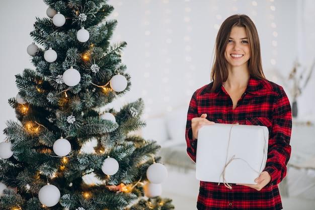 Jeune femme avec boîte-cadeau par l'arbre de noël