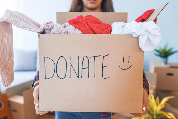 Jeune femme avec une boîte de donation à la maison