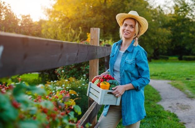 Jeune femme avec une boîte de légumes écologiques frais au coucher du soleil