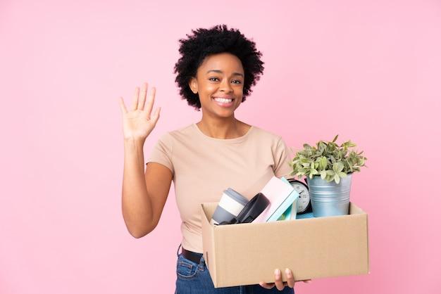 Jeune femme avec boîte pleine de choses sur un mur isolé