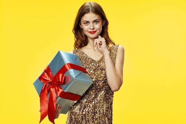 Jeune femme avec des boîtes de cadeaux dans ses mains dans de beaux vêtements, vendant des cadeaux