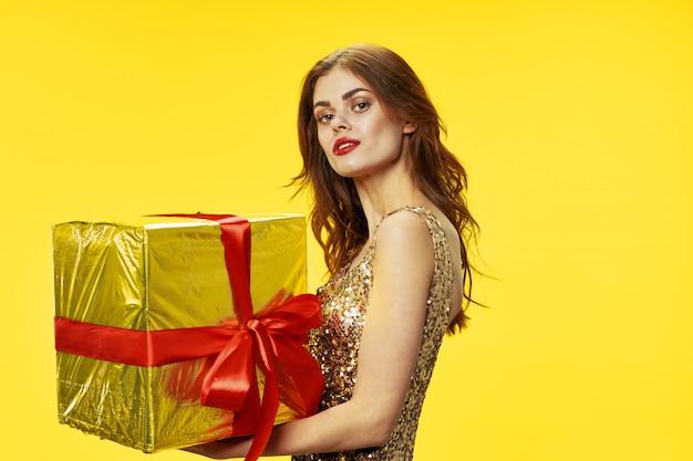 Jeune femme avec des boîtes de cadeaux dans ses mains dans le studio dans de beaux vêtements, vendant des cadeaux, joyeux noël et nouvel an
