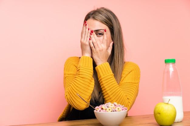 Jeune femme avec bol de céréales couvrant les yeux et regardant à travers les doigts