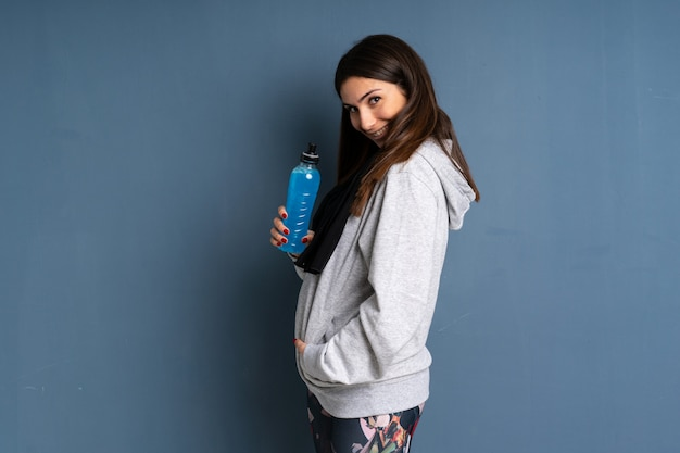 Jeune femme avec bol de céréales debout et regardant sur le côté