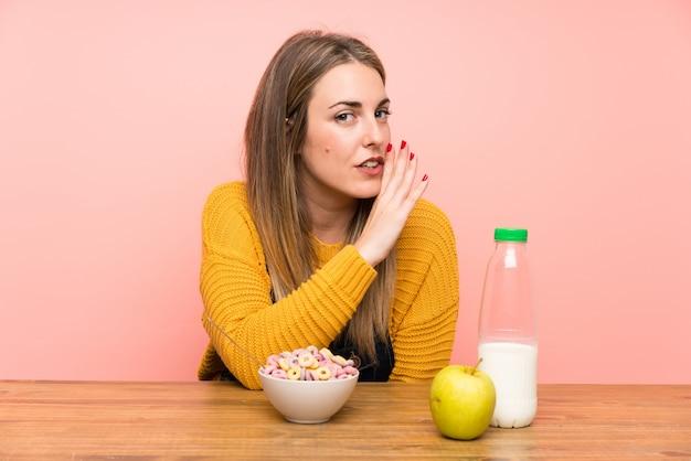 Jeune femme avec un bol de céréales murmurant quelque chose