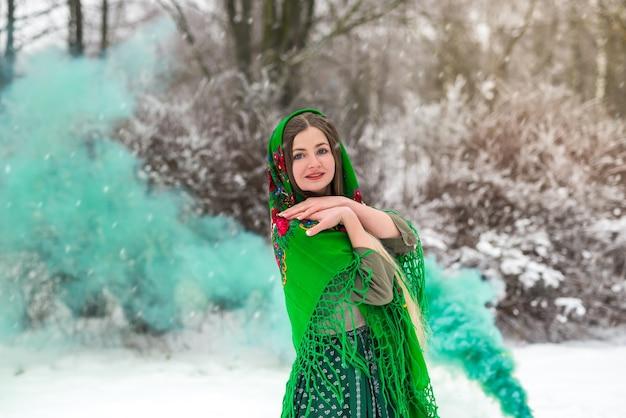 Jeune femme avec une bombe fumigène de couleur verte dans le parc
