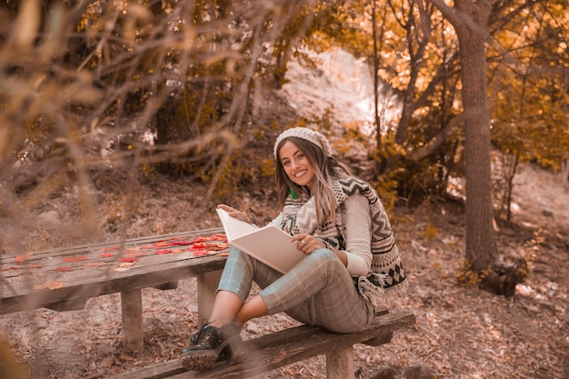 Jeune femme avec un bon livre en automne parc