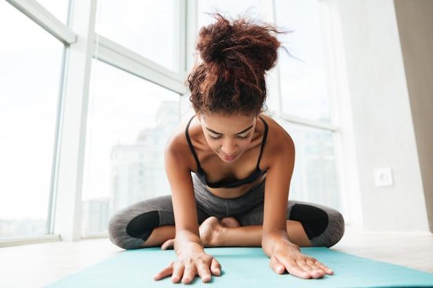Jeune femme en bonne santé, assis en posture de lotus et faire de l'exercice