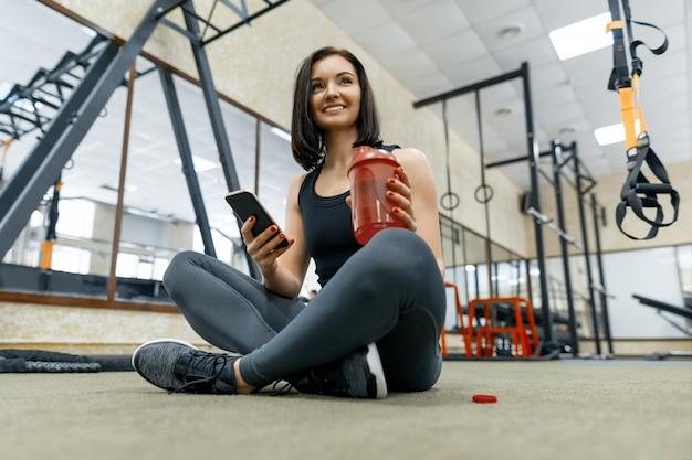Jeune femme en bonne santé avec une bouteille d'eau au repos dans une salle de sport