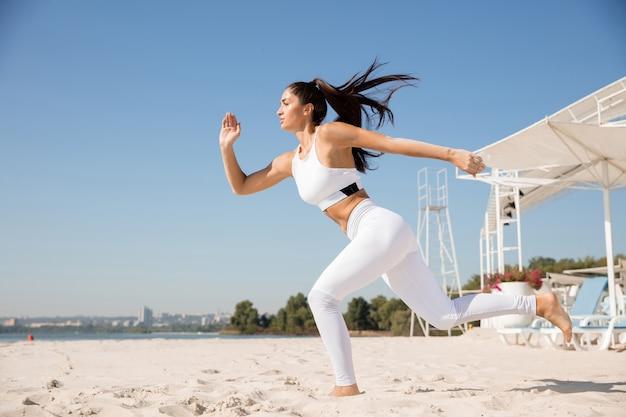 Jeune femme en bonne santé en cours d'exécution et faisant des mouvements brusques à la plage.