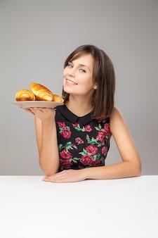 Jeune femme en bonne santé avec des croissants de petit déjeuner en studio