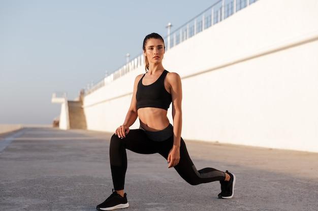 Jeune femme en bonne santé, étirement des jambes et faire des exercices près de la mer