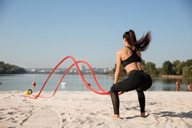 Jeune femme en bonne santé, faire de l'exercice avec les cordes à la plage.