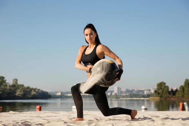 Jeune femme en bonne santé faisant des mouvements brusques avec ballon à la plage