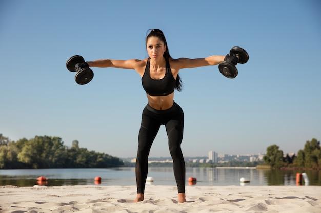 Jeune femme en bonne santé formation haut du corps avec des poids à la plage
