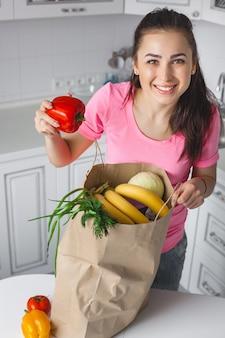 Jeune femme en bonne santé avec des légumes frais dans la cuisine