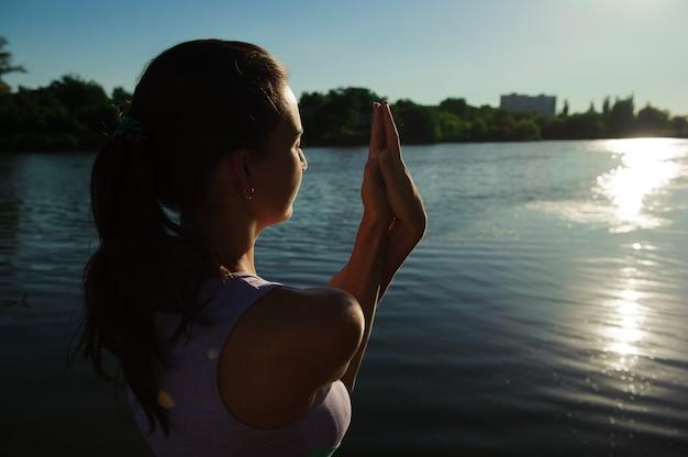 Jeune femme en bonne santé, pratiquer le yoga sur le pont dans la nature.