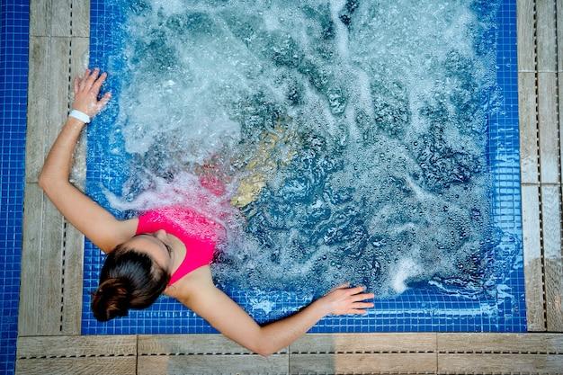 Jeune femme en bonne santé se détendre seule dans la baignoire à la station thermale de bien-être.